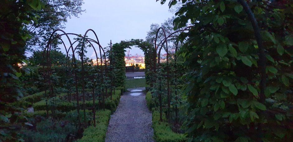 Ein kleiner Park bei schwindendem Tageslicht mit Blick auf den Containerhafen.