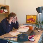 Silke Geisen sitzt am Schreibtisch, vor sich viele Papierstapel und den Laptop, und hält sich den Kopf mit beiden Händen