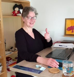"""Silke Geissen sitzt an ihrem ordentlichen Schreibtisch und zeigt strahlend ein """"Daumen hoch"""" zum Ende der FOMO"""