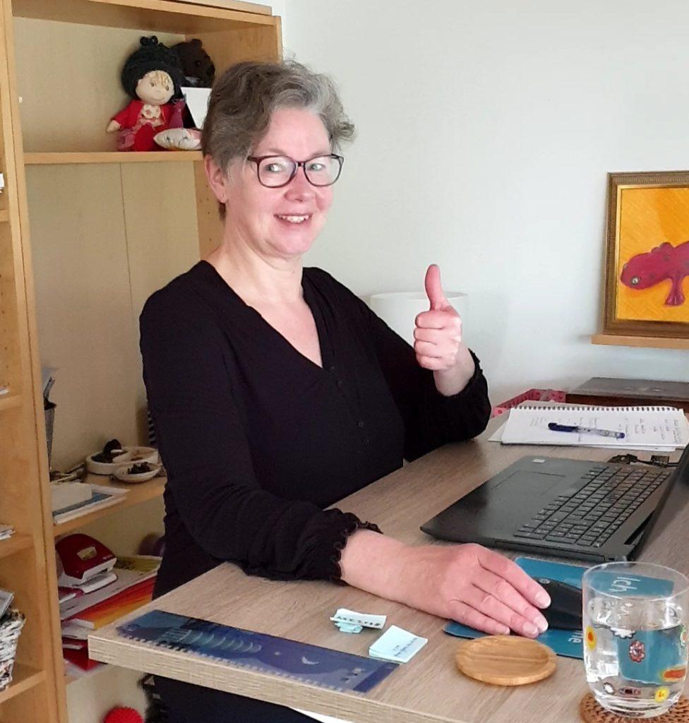 """Silke Geissen sitzt an ihrem ordentlichen Schreibtisch und zeigt strahlend ein """"Daumen hoch"""""""