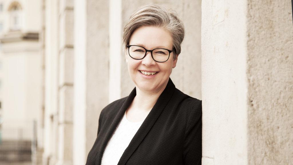 Portraitfoto von Silke Geissen vor einem Backsteingebäude