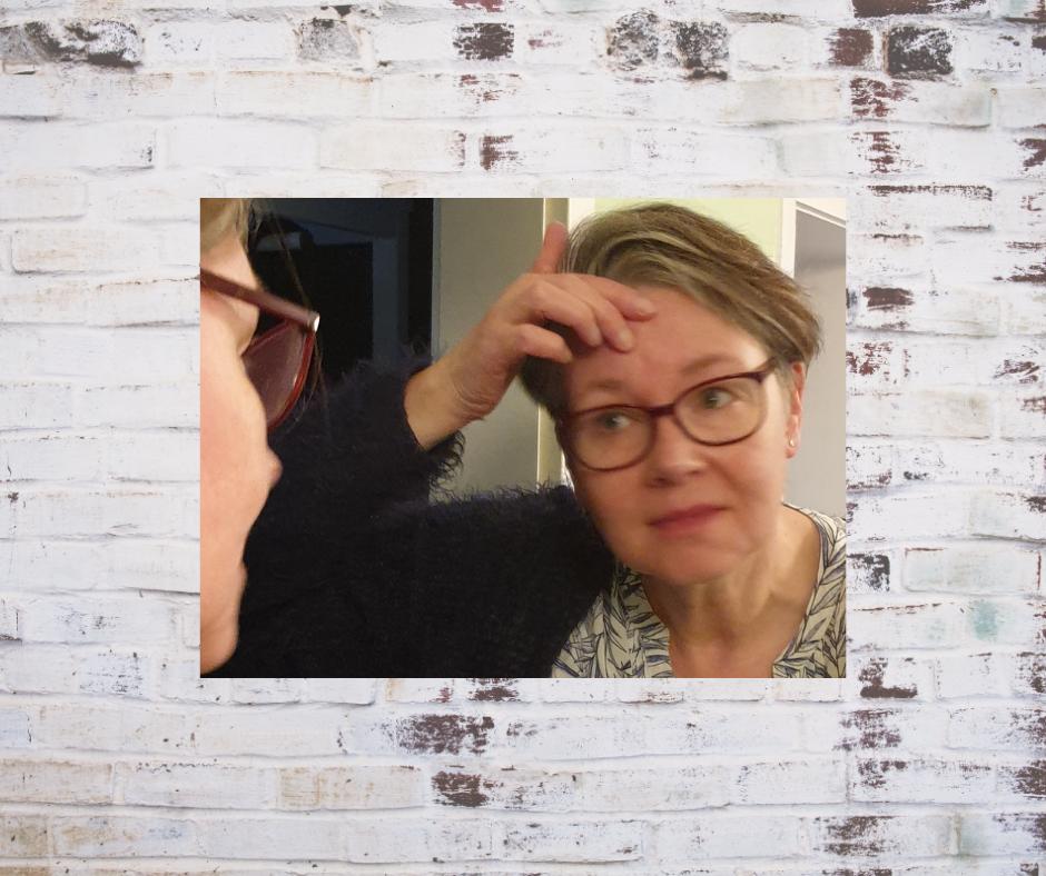 Die Autorin sieht sich ihre Narben im Spiegel an